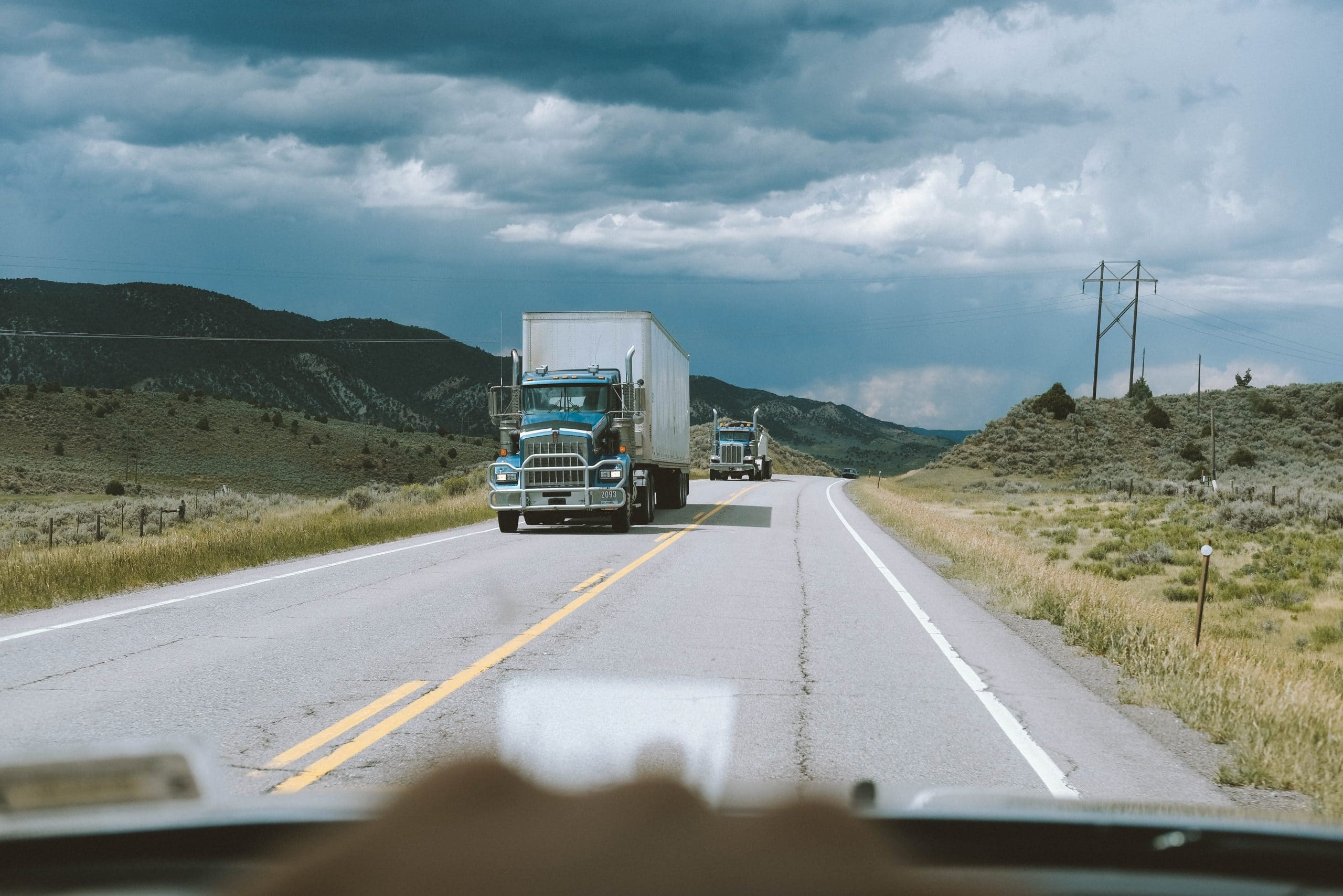 2 tractor trailers driving on single lane highway in midwest town